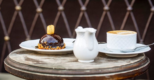 Amare il caffè. tazza di cappuccino fresco. torta al cioccolato. avvicinamento. torta al cioccolato gustosa. cappuccino in tazza, latte caldo, caffè delizioso. pausa caffè. caffè o tazza di caffè al bar al mattino. Foto Premium