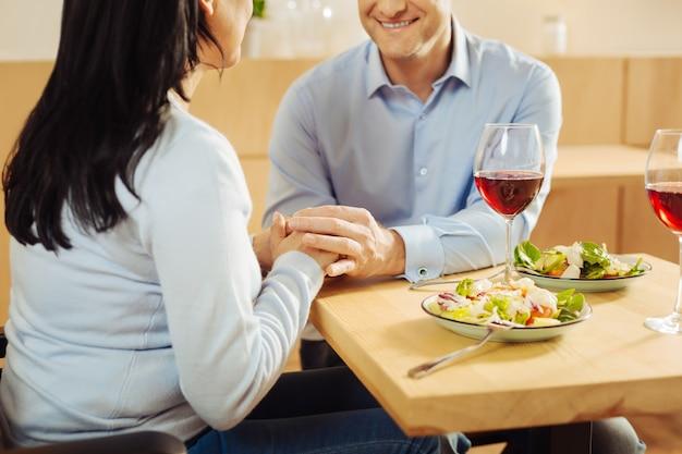 Contenuto amorevole donna disabile e un allegro sorridente uomo ben costruito seduto in un caffè e tenendosi per mano e cenando
