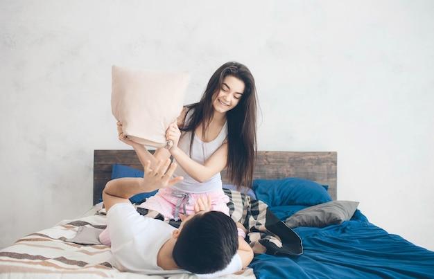 Una coppia di innamorati è sdraiata sul letto. camera da letto luminosa e accogliente. comfort familiare e amore