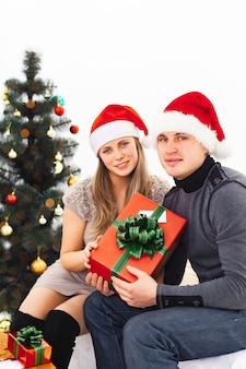 Una coppia di innamorati in cappelli di natale con regali di natale