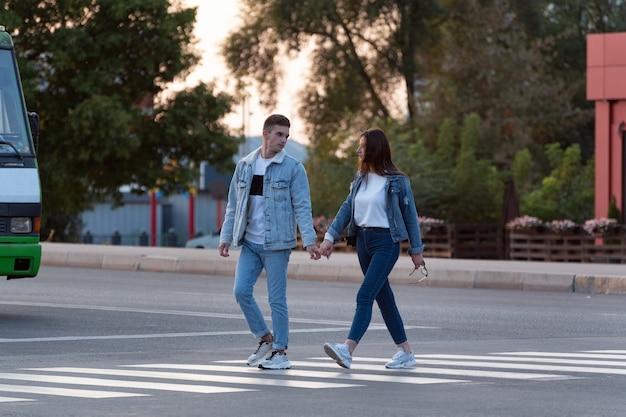 Coppia di innamorati attraversa la strada tenendosi per mano. foto a grandezza naturale.