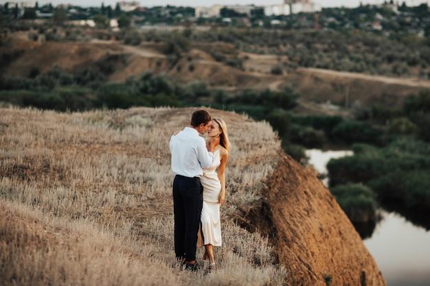 Coppia di innamorati vestiti con abiti eleganti, si abbracciano strettamente.