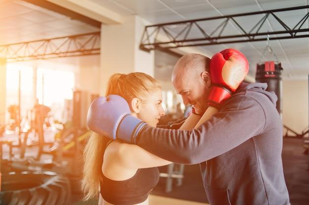 Coppia di innamorati abbraccia in guantoni da boxe e si guarda negli occhi in palestra.