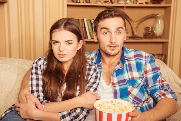 Coppie amorose che abbracciano e che guardano film spaventoso