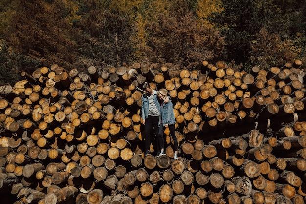 Coppia di innamorati che si abbracciano sorridendo e si sentono felici sui tronchi abbattuti nella foresta.
