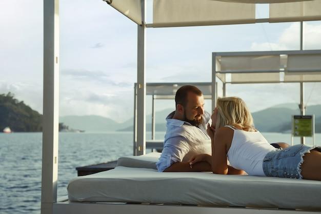 Una coppia di innamorati che si gode la luna di miele in un hotel sulla spiaggia con vista di lusso a piedi mostra emozione sullo sfondo del mare. amanti felici in viaggio romantico divertente la sera delle vacanze estive. concetto romanticismo e relax