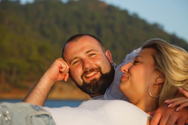 Una coppia di innamorati che si gode la luna di miele in un hotel sulla spiaggia con una vista di lusso che cammina mostra emozione sullo sfondo del mare Foto Premium