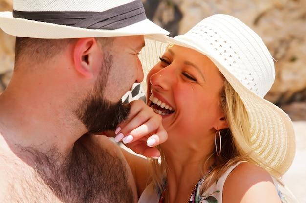 Coppia di innamorati che si godono la luna di miele sulla spiaggia in laguna con vista di lusso camminando su sfondo roccioso