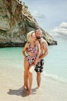 Coppia di innamorati godendo la luna di miele sulla spiaggia in laguna con vista di lusso camminando sullo sfondo del mare. gli amanti felici in viaggio romantico si divertono durante le vacanze estive. concetto romanticismo e relax. copia spazio