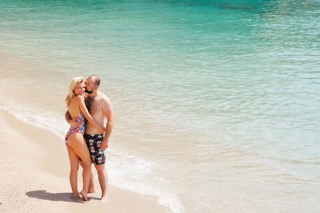 Coppia di innamorati godendo la luna di miele sulla spiaggia in laguna con vista di lusso camminando sullo sfondo del mare