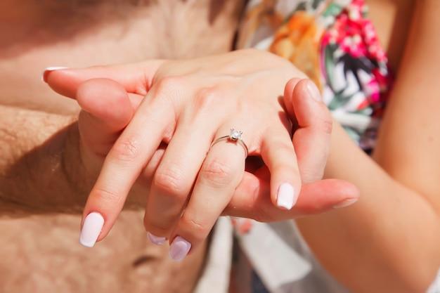 Coppia di innamorati godendo la luna di miele sulla spiaggia in laguna con vista di lusso camminando mostrando l'anello di fidanzamento a portata di mano