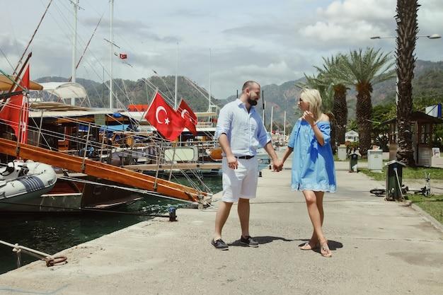 Coppia di innamorati godendo la luna di miele sull'argine con yacht di lusso a piedi attraverso i terreni con bandiera della turchia. gli amanti felici in viaggio romantico si divertono durante le vacanze estive. concetto romanticismo e relax