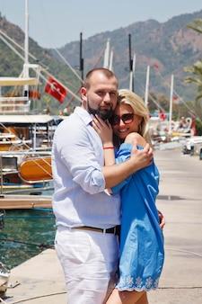 Coppia di innamorati che si godono la luna di miele sull'argine con yacht di lusso