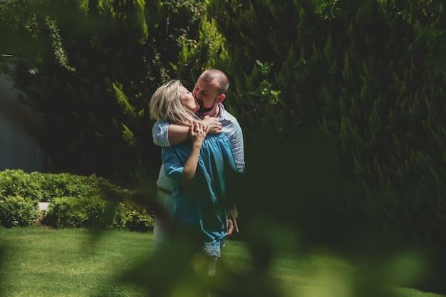 Coppia di innamorati che si godono la luna di miele in un hotel di lusso, passeggiando per i giardini con palme e fiori di bellezza