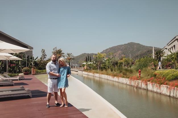 Coppia di innamorati che si godono la luna di miele in un hotel di lusso, passeggiando per giardini con palme e piscina