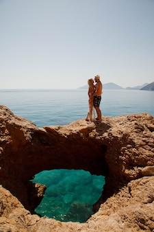 Coppie amorose che si godono la luna di miele su roccia con vista di lusso camminando mostrando emozione sullo sfondo del mare azzurro. gli amanti felici in viaggio romantico si divertono durante le vacanze estive. concetto romanticismo e relax