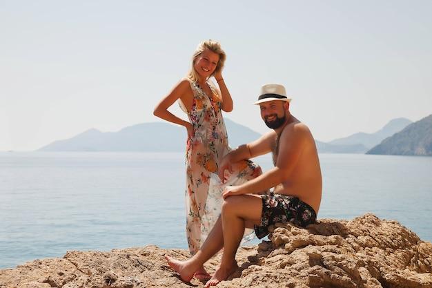 Coppia di innamorati che si godono la luna di miele su roccia con vista di lusso camminando mostrando emozione sullo sfondo del mare azzurro