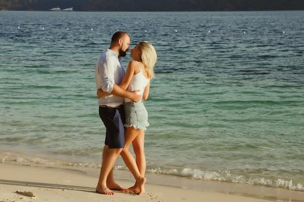 Una coppia di innamorati che si gode la luna di miele in un hotel sulla spiaggia del territorio con vista di lusso a piedi mostra emozione sullo sfondo del mare. amanti felici in viaggio romantico divertente durante le vacanze estive. concetto romanticismo e relax