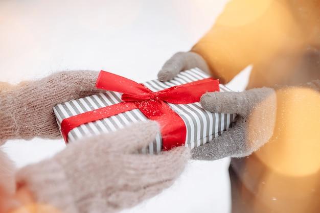 Coppia di innamorati si danno un regalo fuori indossando guanti di lana al parco invernale innevato. scatola a righe con fiocco rosso nelle mani di un uomo e di una donna. concetto di san valentino. giornata della donna.