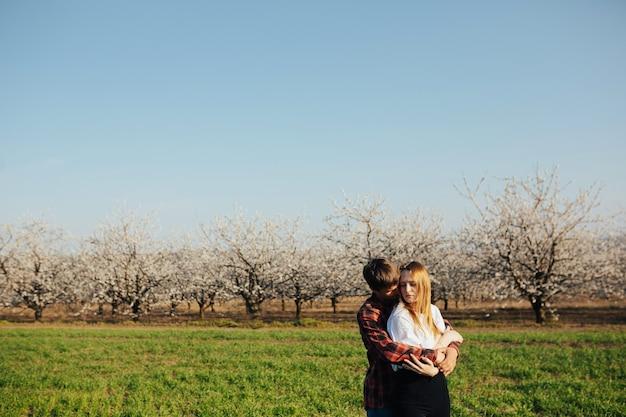 Coppia di innamorati su un prato verde sta abbracciando con alberi in fiore sul muro nella giornata di sole primaverile.
