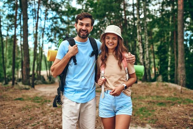 Un'amorevole coppia di escursionisti sta con gli zaini sullo sfondo della foresta. campeggio, viaggi, escursioni.
