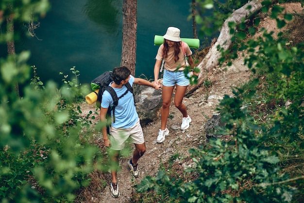 Un'amorevole coppia di escursionisti con zaini cammina attraverso la foresta vicino al fiume. campeggio, viaggi, escursioni.