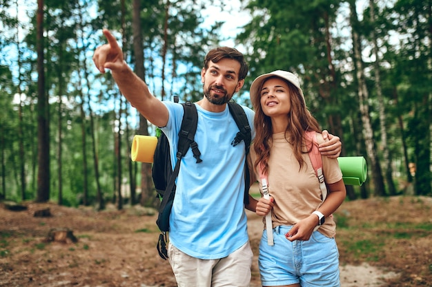 Un'amorevole coppia di escursionisti con zaini cammina attraverso una pineta. campeggio, viaggi, escursioni.