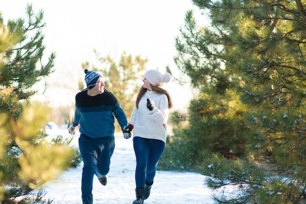 Una coppia amorosa tenendosi per mano attraversa la foresta dell'inverno. ridi e divertiti