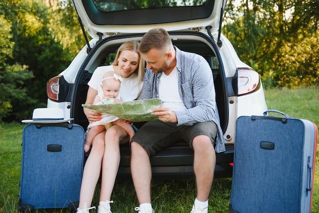 Coppia di innamorati che si abbracciano seduti nel bagagliaio dell'auto guardando la mappa in viaggio
