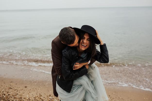 Coppia di innamorati si diverte e si abbraccia sulla spiaggia di sabbia vuota del mare.