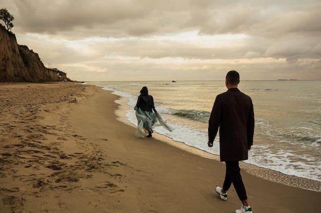 Una coppia di innamorati si diverte e cammina sulla spiaggia sabbiosa vuota del mare con cielo nuvoloso in superficie.