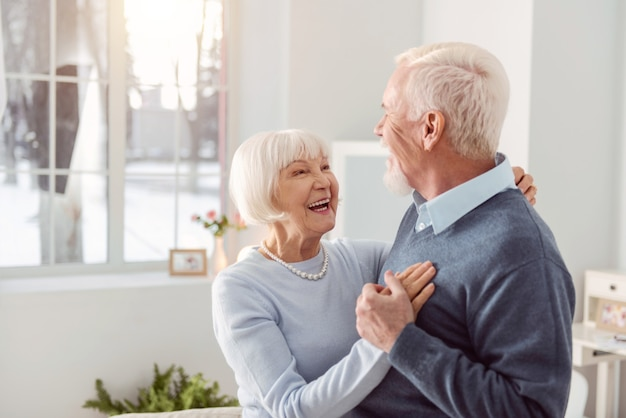 Coppia di innamorati. gioioso marito e moglie anziani che ballano nel soggiorno mentre si sorridono ampiamente