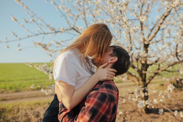 Coppia di innamorati baci e abbracci vicino all'albero in fiore in primavera.