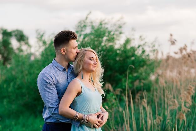 Coppia di innamorati baci sulla natura, sera d'estate, tramonto