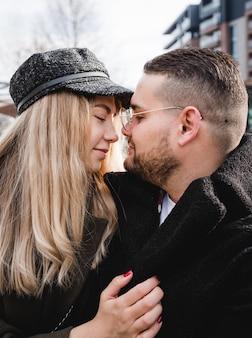 Baciare amoroso delle coppie all'aperto. la coppia sveglia dei pantaloni a vita bassa sta camminando nel parco di primavera