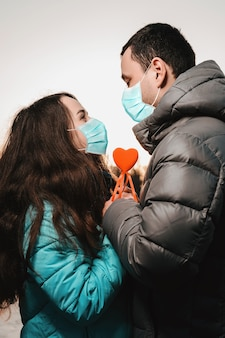 Coppia di innamorati in maschera medica mano nella mano nel parco durante la quarantena e la pandemia di coronavirus 2021