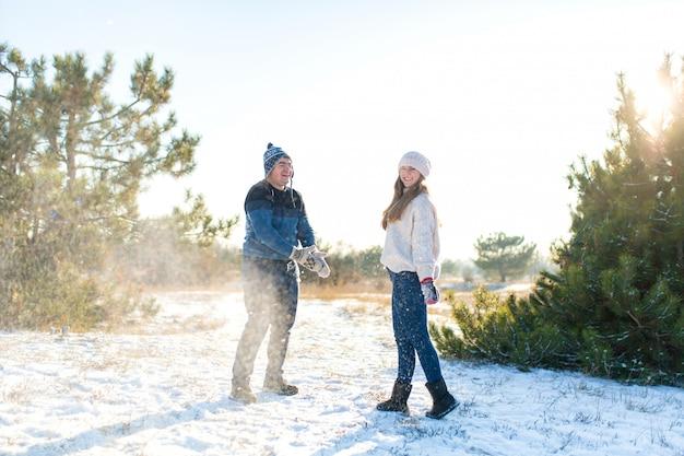 Le coppie amorose giocano a palle di neve in inverno nella foresta. lancia l'un l'altro la neve. ridi e divertiti