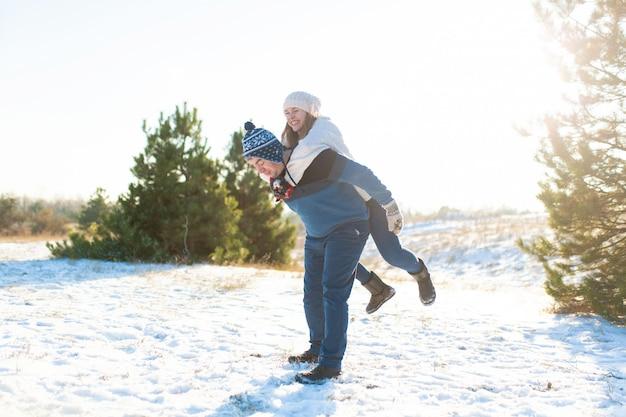 Coppia di innamorati gioca in inverno nella foresta.