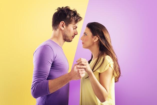 Coppia di innamorati pronti a baciarsi su viola e giallo