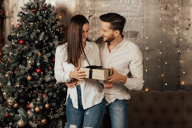 Coppia di innamorati in piedi nel soggiorno accanto a un albero di natale splendidamente decorato con ghirlanda. la donna ha ricevuto un regalo dall'uomo.