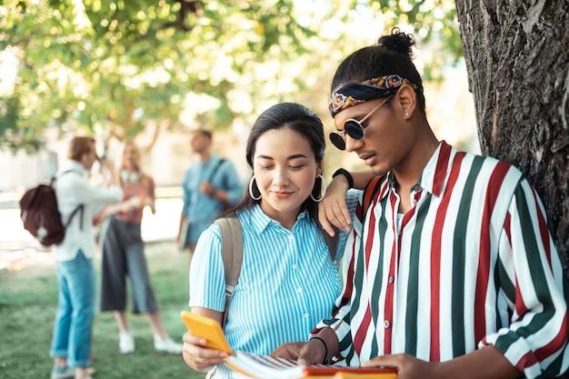 Coppia di innamorati in piedi sotto l'albero nel cortile dell'università davanti ai loro amici universitari