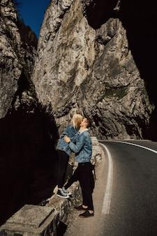 Coppia di innamorati di turisti che si abbracciano e si baciano vicino a pietre e rocce in montagna.