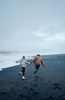 Una coppia di turisti innamorati che si tengono per mano si divertono passeggiando lungo la spiaggia di sabbia nera vulcanica e ammirano le grandi onde dell'oceano.