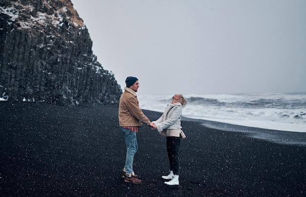 Una coppia di turisti innamorati che si tengono per mano guarda la neve che cade, si diverte a passeggiare lungo la spiaggia con sabbia nera vulcanica e ammira le grandi onde dell'oceano.