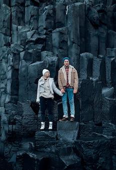 Coppia di innamorati di turisti stanno mano nella mano sulle pietre delle montagne di basalto vulcanico nero.