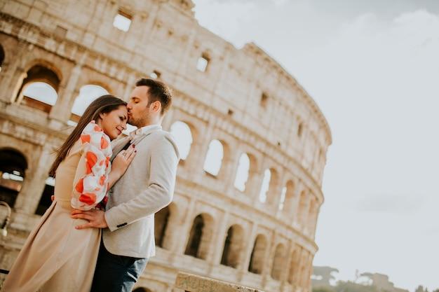 Coppie amorose che visitano i punti di riferimento famosi italiani colosseum a roma, italia