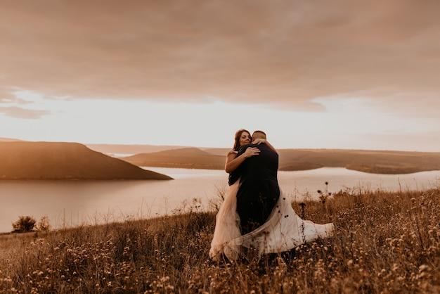 Coppia di innamorati matrimonio sposi novelli in abito bianco e vestito abbraccio baci vortice sull'erba alta nel campo estivo sulla montagna sopra il fiume