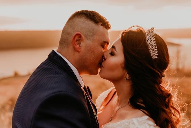 Una coppia di innamorati matrimonio sposi novelli in abito bianco e vestito a piedi abbraccio baci vortice sull'erba alta nel campo estivo sulla montagna sopra il fiume