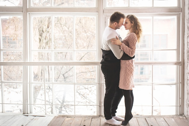 Coppia di innamorati in abiti invernali vicino alla finestra