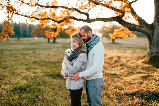 Coppie amorose con l'animale domestico divertente che abbraccia nel campo al tramonto.